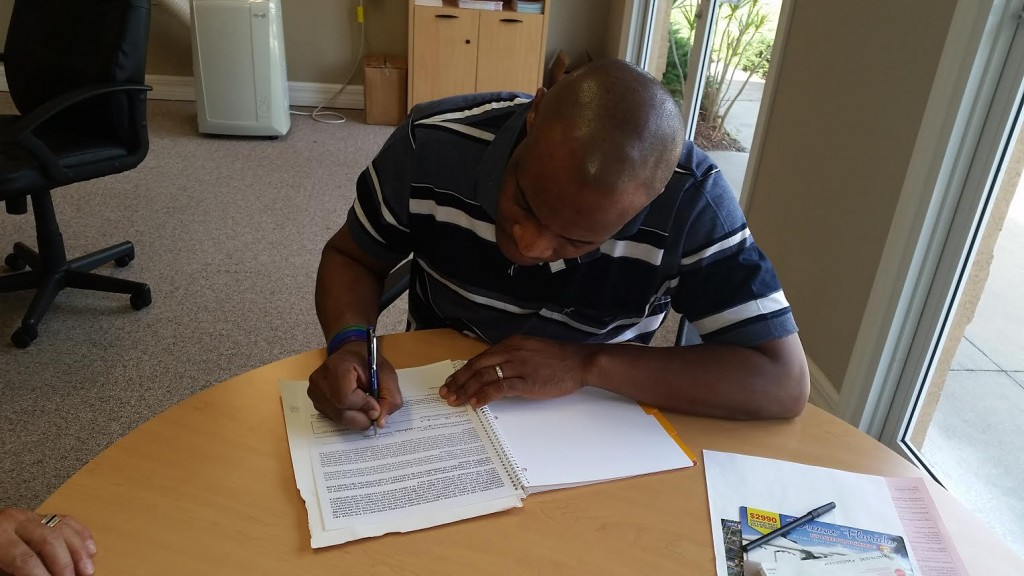 Customer signing his contract for the land he is purchasing and he will get his deed from the Florida Court house with his land purchase in 90 days